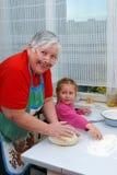De grootmoeder en de kleindochter kneden het deeg royalty-vrije stock fotografie