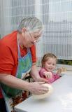 De grootmoeder en de kleindochter kneden het deeg Royalty-vrije Stock Afbeelding