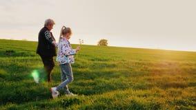 De grootmoeder en de kleindochter lopen rond het platteland Zij lopen langs de landweg bij zonsondergang activiteit stock video