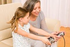 De grootmoeder en de kleindochter spelen computerspel royalty-vrije stock afbeelding
