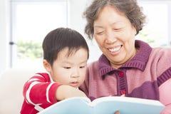 De grootmoeder en de kleinzoon lezen samen verhaalboek Stock Afbeeldingen