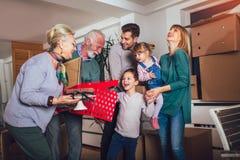 De grootmoeder en de grootvader brengen een gift voor zich het bewegen in een nieuwe flat aan kinderen stock foto