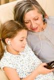De grootmoeder en het jonge meisje luisteren samen muziek royalty-vrije stock foto