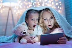 De grootmoeder en de kleindochter letten thuis op film op tablet onder deken bij nacht stock afbeeldingen