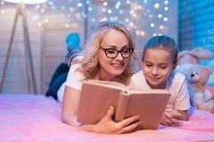 De grootmoeder en de kleindochter lezen thuis boek vóór slaap bij nacht royalty-vrije stock afbeelding