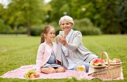 De grootmoeder en de kleindochter nemen selfie bij park stock afbeeldingen