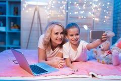 De grootmoeder en de kleindochter nemen thuis selfie bij nacht royalty-vrije stock foto's