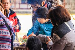 De grootmoeder helpt een klein meisje om een kaars in een Boeddhistische tempel aan te steken en te plaatsen stock foto