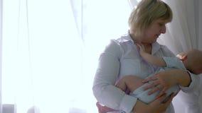 De grootmoeder houdt baby in wapens op achtergrond van venster in backlight bij ruimte stock videobeelden