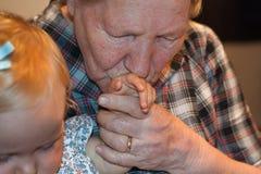 De grootmoeder kust haar kleindochtershand Stock Foto's