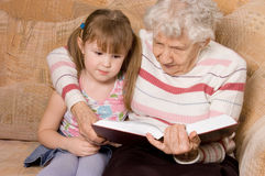 De grootmoeder met de kleindochter las het boek Royalty-vrije Stock Afbeelding