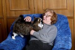 De grootmoeder met een kat binnenshuis stock afbeeldingen