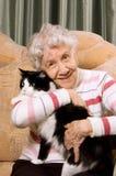 De grootmoeder met een kat op een bank Royalty-vrije Stock Afbeeldingen