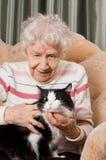 De grootmoeder met een kat op een bank royalty-vrije stock afbeelding