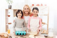 De grootmoeder met haar kleinkinderen kookt gebakjes in keuken Het mengsel van het chocoladekoekje, het bakken de vormen en het s royalty-vrije stock afbeelding