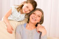 De grootmoeder met jonge meisjesglimlach ontspant samen stock afbeelding