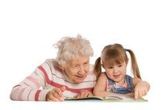 De grootmoeder met kleindochter las het boek stock foto's