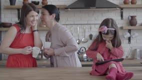 De grootmoeder, de moeder en weinig daghter zijn samen in de keuken Het meisje die op tabletzitting spelen op de lijst stock videobeelden