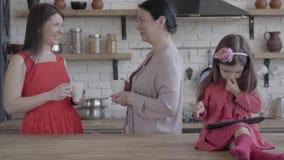 De grootmoeder, de moeder en weinig dochter zijn samen in een moderne keuken De de tabletzitting van de meisjesholding op de lijs stock videobeelden
