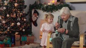 De grootmoeder onderwijst om haar kleindochter te breien stock footage