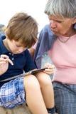 De grootmoeder van het kindonderwijs hoe te om tablet te gebruiken Stock Afbeeldingen