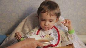 De grootmoeder voedt het kind stock video