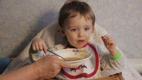 De grootmoeder voedt het kind stock footage