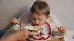 De grootmoeder voedt het kind stock videobeelden