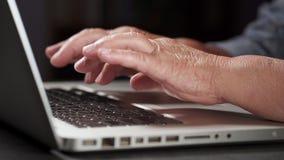 De grootmoeder werkt achter laptop, typend aan toetsenbord met haar oude handen met rimpels Moderne oude gepensioneerde die werke stock footage