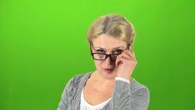 De grootmoeder zet op haar glazen en spreekt stiller Het groene scherm stock videobeelden