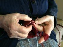 De grootmoederhanden breien rood wolgaren Hogere dame, oma in blauwe gebreide met de hand gemaakte sweater naaldpatroon van draad royalty-vrije stock afbeeldingen
