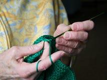 De grootmoedershanden haken groen garen Close-upklem van het hogere vrouw haken stock foto