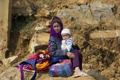 De grootmoederzitting van bloemhmong in de zon op rots met mollige baby op haar knieën stock afbeelding