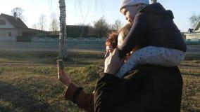 De grootvader en de grootmoeder met haar kleinzoon lopen in het park en de bespreking op de mobiele telefoon met hun verwanten bi stock videobeelden