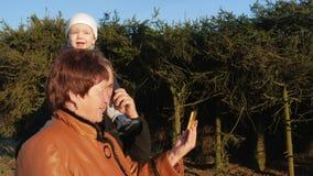 De grootvader en de grootmoeder met haar kleinzoon lopen in het park en de bespreking op de mobiele telefoon met hun verwanten bi stock video