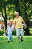 De grootvader en het kind hebben pret in park Royalty-vrije Stock Afbeelding