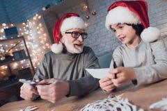 De grootvader en de kleinzoon maken thuis Kerstmisdecoratie bij nacht stock foto's