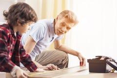 De grootvader en de kleinzoon meten lijst met het meten van band Royalty-vrije Stock Afbeelding