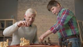 De grootvader en de kleinzoon treffen voorbereidingen om schaak te spelen Een bejaarde onderwijst een vet kind hoe te om schaak t stock video