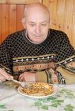 De grootvader ging zitten bij een lijst en eet hete pannekoek met eetlust stock fotografie