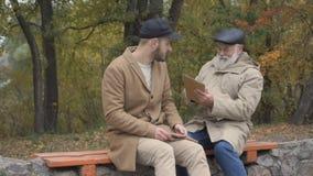 De grootvader haalt een tablet van handen van kleinzoon weg stock videobeelden