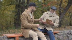 De grootvader haalt een tablet van kleinzoonhanden weg stock video