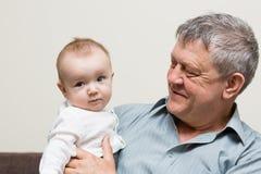 De grootvader houdt de kleinzoon op zijn handen stock foto
