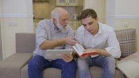 De grootvader overtuigt kleinzoon dat gebruiken van tablet beter is dan lezingsboek stock video