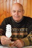 De grootvader zit bij een lijst waarop om te liggen de calculator en het geld, document nota's en muntstukken royalty-vrije stock foto's