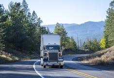De grote Amerikaanse semi vrachtwagen die van de installatie klassieke bonnet goederen binnen vervoeren stock afbeelding