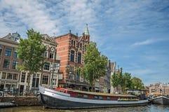 De grote boot legde aan kant van tree-lined kanaal, baksteengebouwen en zonnige blauwe hemel in Amsterdam vast Royalty-vrije Stock Foto's