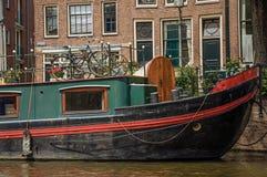 De grote boot legde aan kant van tree-lined kanaal, oude gebouwen en zonnige blauwe hemel in Amsterdam vast Royalty-vrije Stock Foto