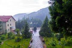 De grote dalingen van regen vallen op het huis met een klein park rond het stock foto