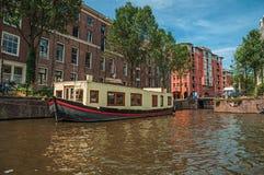 De grote die boot als huis wordt gebruikt legde aan kant van tree-lined kanaal met oude gebouwen en zonnige blauwe hemel in Amste Stock Fotografie